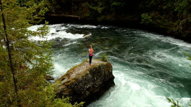 athletic woman practicing yoga at a powerful river - yoga stock videos & royalty-free footage