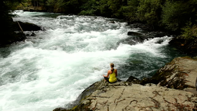 athletic woman practicing yoga at a powerful river - one mid adult woman only stock videos & royalty-free footage