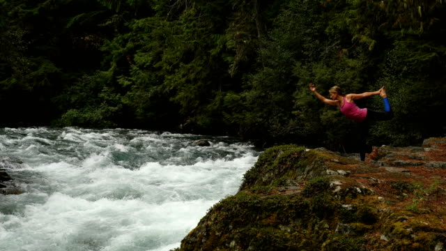 Athletic woman practicing yoga at a powerful river