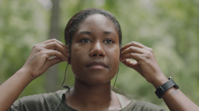 slow mo. cu. athletic woman prepares to run in a forest by putting earbuds in and checking her smartwatch - making stock videos & royalty-free footage
