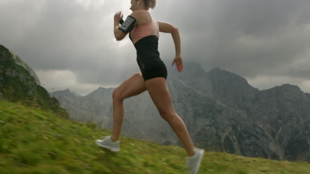slo mo athletic woman running on the top of a mountain ridge - side view stock videos & royalty-free footage
