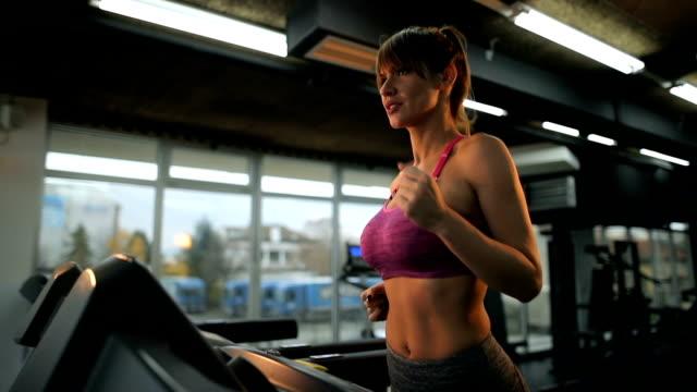 vídeos de stock, filmes e b-roll de atlética mulher correndo na esteira na academia de ginástica. - sutiã para esportes