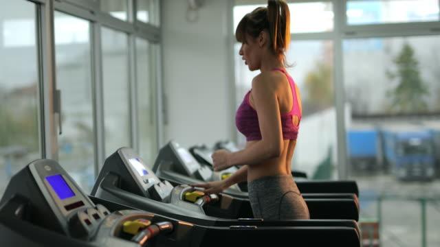 Athletic woman running on treadmill in a health club.