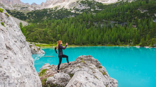 athletic woman running up a mountain rock, stopping at the edge, enjoying the view of a beautiful lake - cross country running stock videos & royalty-free footage