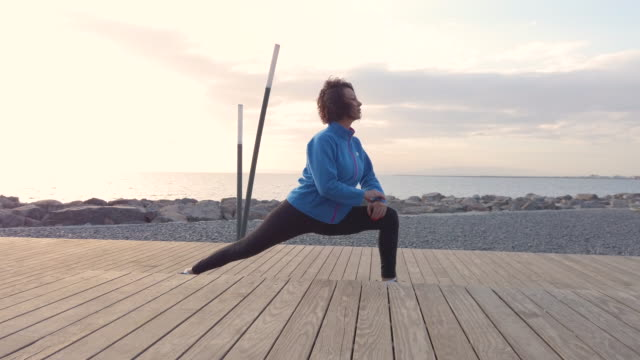 athletic woman stretching at seaside - self discipline stock videos & royalty-free footage