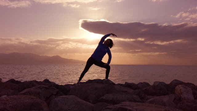 athletic woman stretching at seaside - 40 44 years stock videos & royalty-free footage