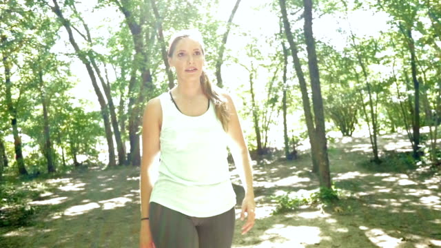 stockvideo's en b-roll-footage met athletic woman stretching muscles and running off road in park - haarband