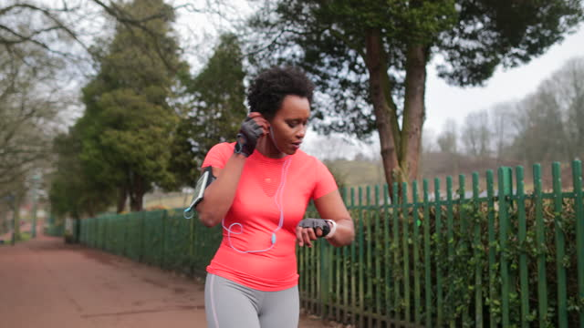 athletic woman using smart phone and smart watch while running - boundary stock videos & royalty-free footage
