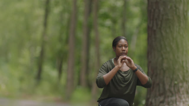 slow mo. athletic woman wearing earbuds checks her smartwatch before doing lunges on a path in the forest - african american ethnicity stock videos & royalty-free footage