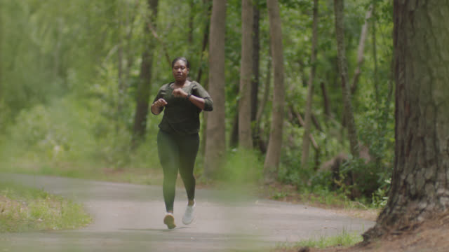 slow mo. athletic woman wearing earbuds stops running in the forest to check her smartwatch - smartwatch video stock e b–roll