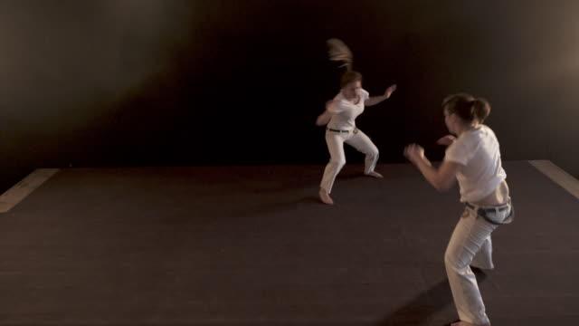 Atletische vrouwen vechten op capoeira opleiding in een healthclub.