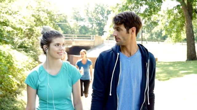 vídeos y material grabado en eventos de stock de atlético joven pareja caminando juntos en la pista en el parque soleado - pedestrismo