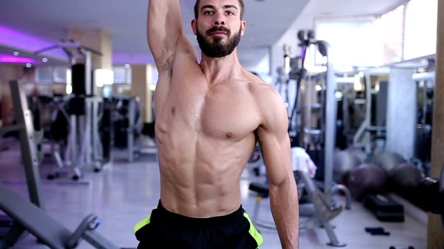 Athletic Young Male Does Dumbbell Exercises at Gym