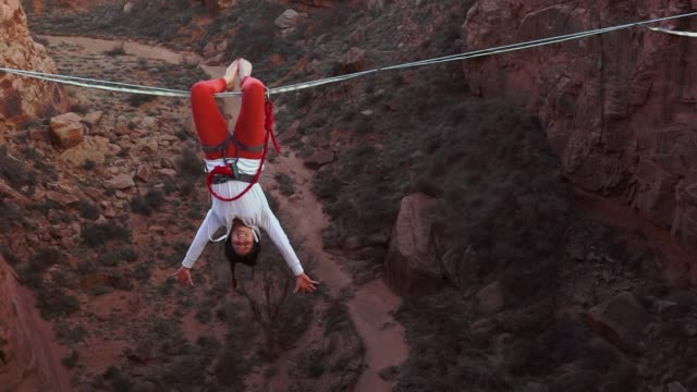 athletic young woman highlining over a canyon in moab - tightrope stock videos & royalty-free footage