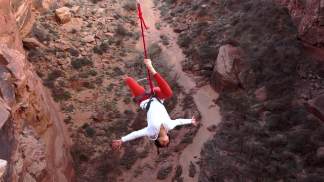 Atletische jonge vrouw Highlining boven een Canyon in Moab