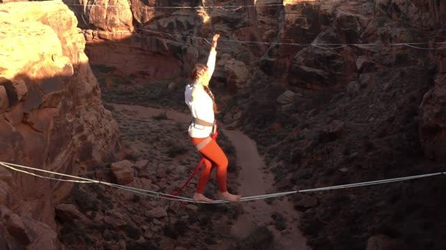 vídeos de stock e filmes b-roll de athletic young woman highlining over a canyon in moab - corda