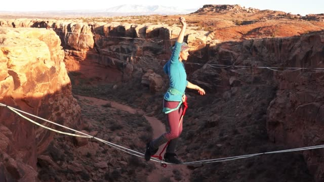 athletic young woman highlining over a canyon in moab - moab utah stock videos & royalty-free footage