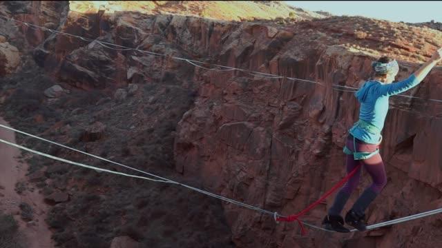 Sportliche junge Frau Highlining über eine Schlucht in Moab