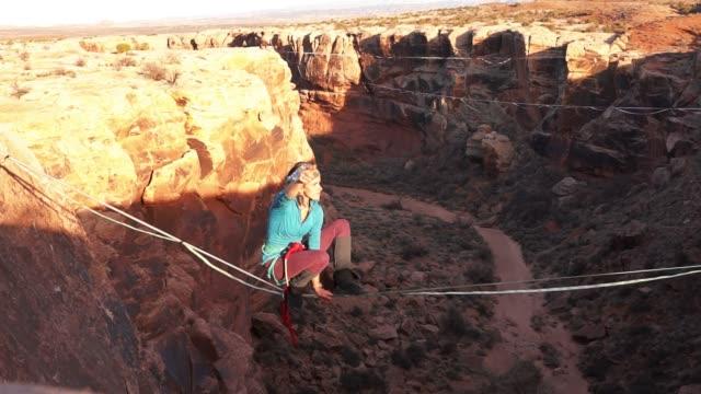 sportliche junge frau highlining über eine schlucht in moab - gleichgewicht stock-videos und b-roll-filmmaterial