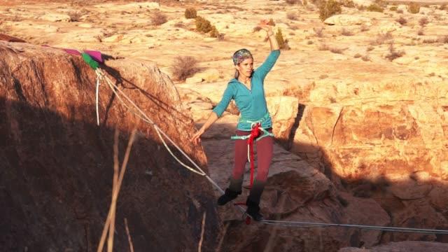 vídeos y material grabado en eventos de stock de joven atlético highlining sobre un cañón en moab - alambre
