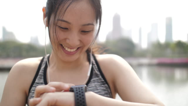 athletic young woman monitoring her running performance on smartwatch - interval start stock videos & royalty-free footage