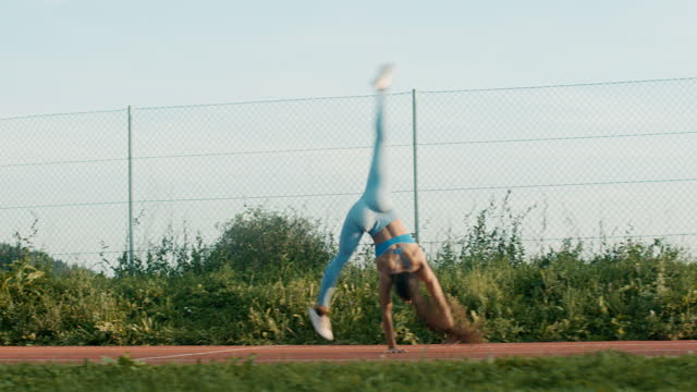 slo mo athletic young woman practicing cartwheel on a running track - gymnastics stock videos & royalty-free footage