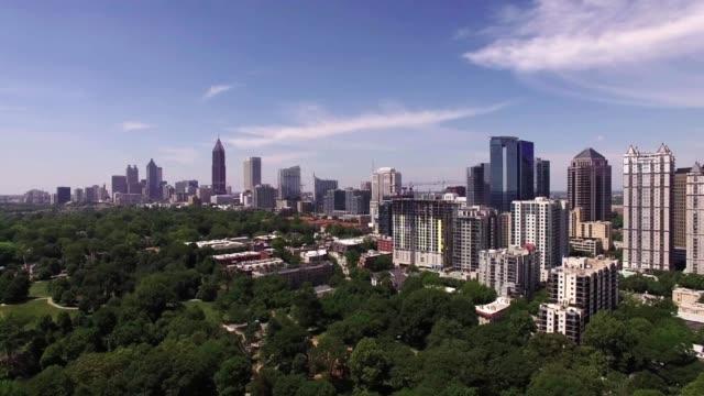 atlanta aerial flying over park towards city skyscraper - atlanta stock videos and b-roll footage