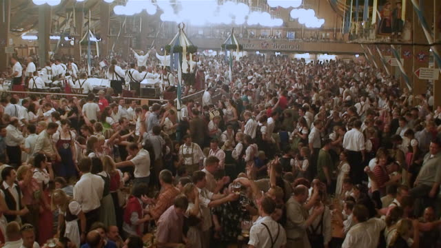 ms atmosphere are inside traditional beer tent, people are singing and dancing on tables on oktoberfest / munich, bavaria, germany - baviera video stock e b–roll