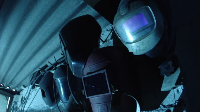 [FLASHING IMAGE] Atmospheric blue light created by welding flashes over protective masks hanging in a blacksmithing workshop.