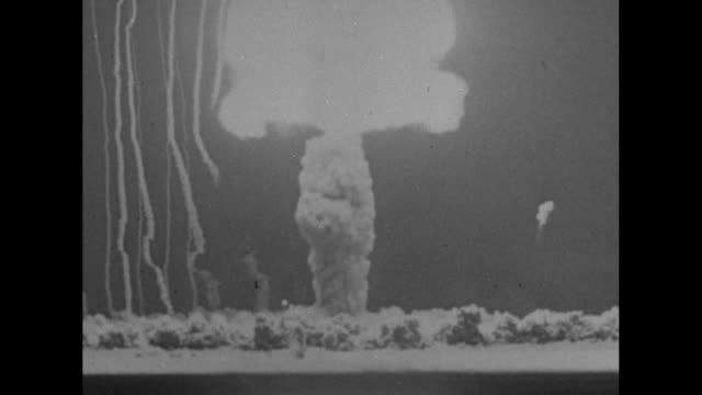 vidéos et rushes de atomic bomb blast / two shots of yucca flat site of atomic bomb tests / two shots of atomic bomb blasts / dust from blast blowing past airplanes... - terrorisme