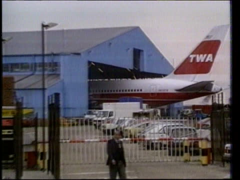 Atomic trigger trial ENGLAND London Heathrow Airport LMS Tail end of TWA Boeing protruding from hangar CMS Man up steps and on to TWA Boeing 747