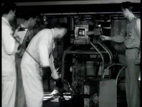 Atomic workers removing piston ring from graphite holder shield MS Geiger counter CU Tool pulling piston rings out of shield