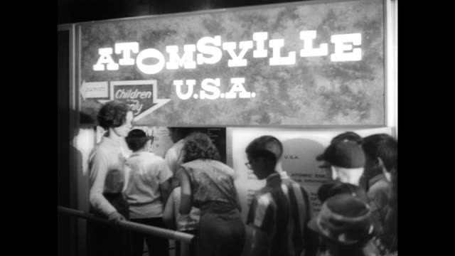 vídeos de stock, filmes e b-roll de / atomsville usa exhibit for children at the world's fair / children manipulate atomic devices / looking for uranium game / little girl gets her... - 1964