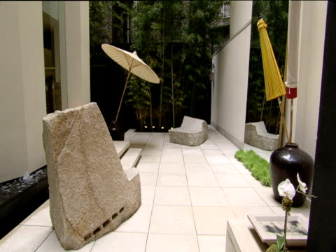 Atrium of designer boutique with stone seats and bubbling water feature New York
