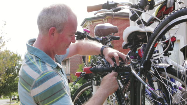 attaching bikes to a bike rack - rack stock videos & royalty-free footage