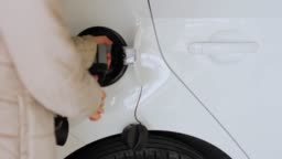 Attaching power cable to electric car by woman in a light closes. Charging of electric vehicle EV.