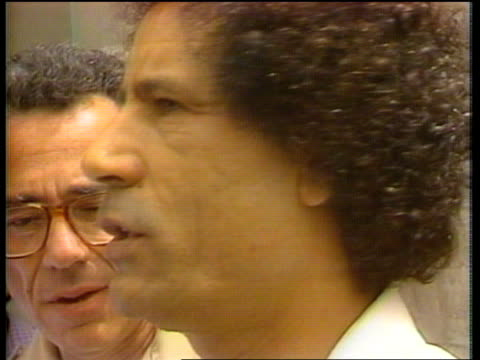 vídeos de stock, filmes e b-roll de colonel gaddafi interview libya tripoli shot along road tracking shot through street colonel muammar algaddafi standing in steet and then along road... - líbia