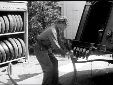 service station delivery attendant in company uniform climbing onto standard oil gas delivery tank truck ms hooking up hose to valve cu gas hose... - gas station attendant stock videos and b-roll footage
