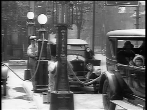 vídeos de stock, filmes e b-roll de b/w 1929 attendants pumping gas at gas station / newsreel - 1920 1929