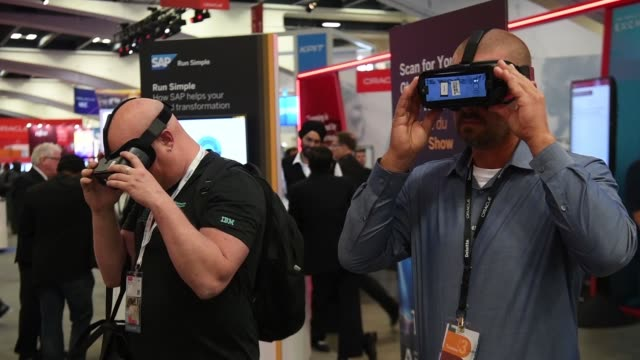 attendees demo vr headsets at the oracle openworld 2017 conference and pass large signage in san francisco california us on monday oct 2 2017... - oracle corporation stock-videos und b-roll-filmmaterial