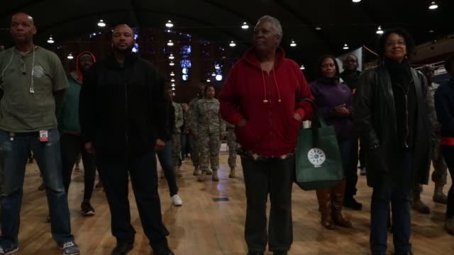 attendees listen to remarks during an operation homefront event to distribute holiday meals at the dc national guard armory - waffenlager stock-videos und b-roll-filmmaterial