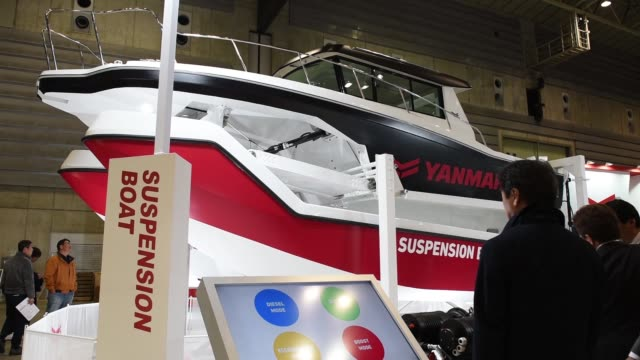 Attendees look at a Yanmar Co suspension boat at the Japan International Boat Show in Yokohama Japan on Thursday March 8 a technician makes...