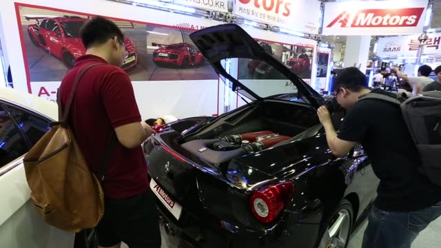 attendees look at customized vehicles at the seoul auto salon 2013 in seoul south korea on thursday july 11 attendees look at a customized ferrari... - customised stock videos & royalty-free footage
