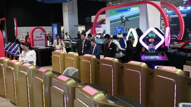 Attendees look at gaming machines during the Macau Gaming Show in Macau China on Tuesday Nov 14 Close up attendees look at online games made by LT...