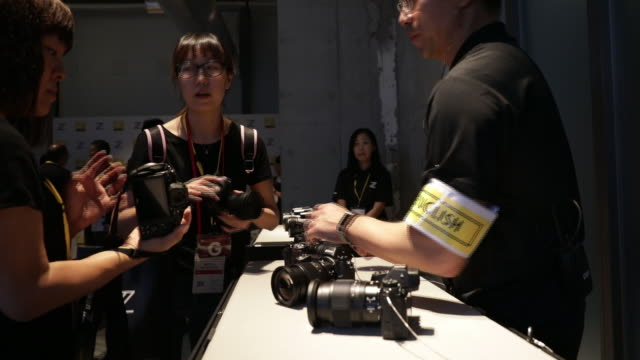 attendees of news conference trying out a z7 mirrorless digital camera from nikon corporation in in tokyo japan on thursday august 2018 - digital camera stock videos and b-roll footage