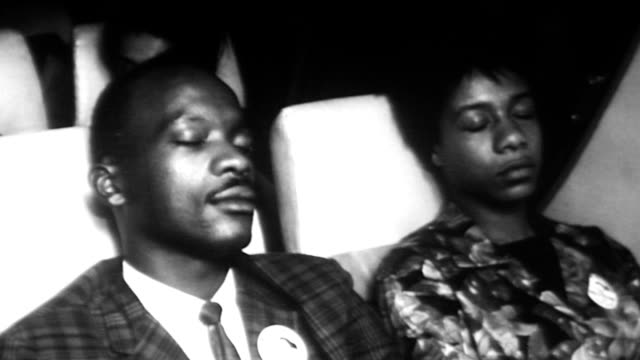 vídeos de stock e filmes b-roll de attendees of the civil rights march on washington leave on a bus / tired attendees sleeping on bus as they go home after the march august 28 1963 in... - 1963