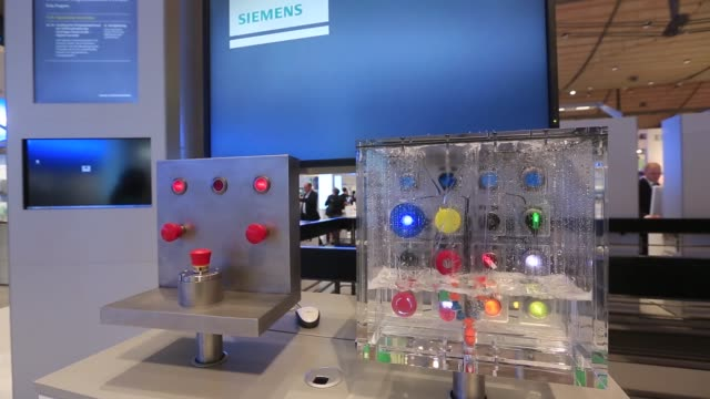 Attendees pass the Siemens AG exhibition trade stand at the Hanover industrial fair in Hanover Germany on Monday April 13 2015 SHOTS demonstration of...
