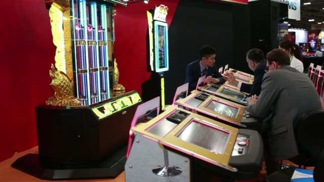 attendees play at an electronic gaming table, attendees play gaming machines, roulette ball in a slot on a spinning roulette wheel, a croupier spins... - macao stock videos & royalty-free footage