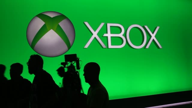 attendees play of xbox games at the e3 electronic entertainment expo in los angeles california us attendees pass by a giant xbox logo and signage at... - xbox stock videos & royalty-free footage