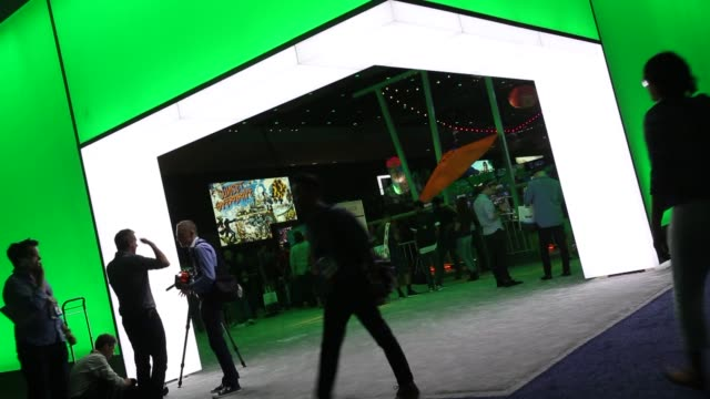 Attendees play of XBOX games at the E3 Electronic Entertainment Expo in Los Angeles California US attendees pass by a giant Xbox logo and signage at...